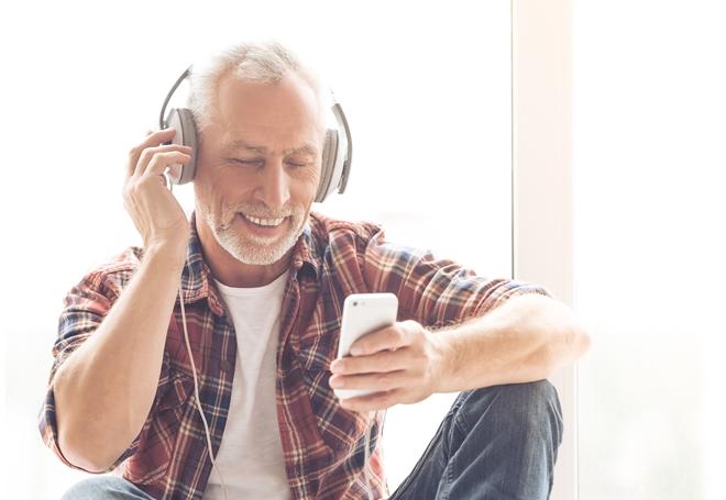 Man die luistert naar de audiokrant.